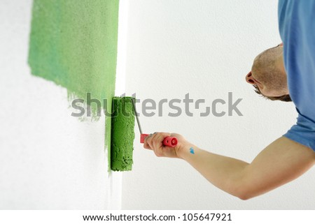 handsome young man paint in blue and green color  white wall of new home