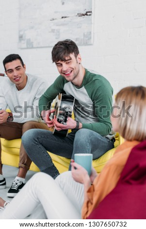 handsome young man playing guitar for multiethnic friends