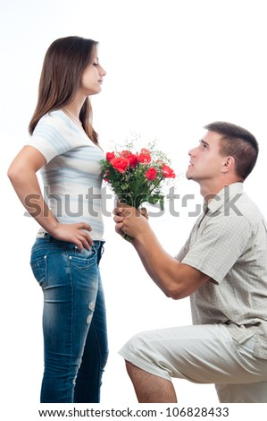 Handsome young man pleading for forgiveness and offering bouquet of roses to his girlfriend.