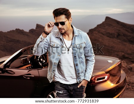 Handsome, young man posing next to his luxurious convertible car