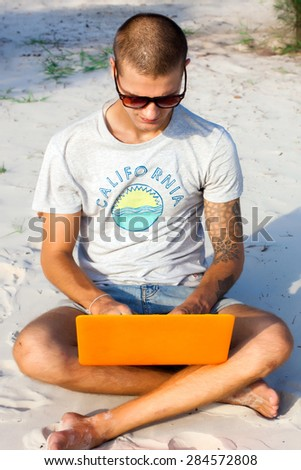 Handsome young man posing on the  beach and working on laptop on internet. Freelance work,travel concept,hike man,social network,man with computer on the beach,working on the beach of tropical island