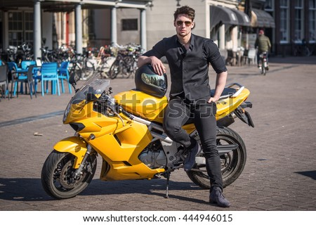 Handsome young man posing with yellow motorcycle on city road against European urban buildings. Attractive male model on a bike wearing black clothes.