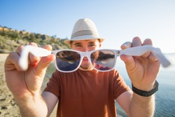Handsome young man puts on camera sunglasses on the beach. Travel, fun, summer and vacation concept