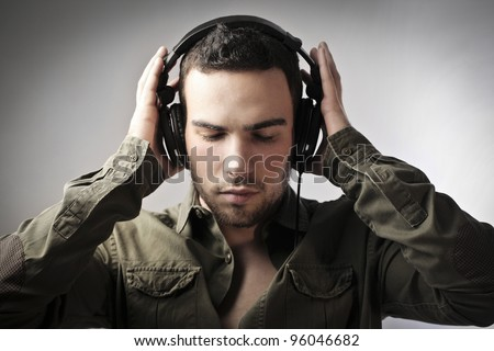 Handsome young man putting on headphones - stock photo