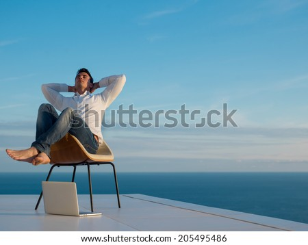 handsome young man relaxing and working on laptop computer at home balcony while looking sunset #205495486