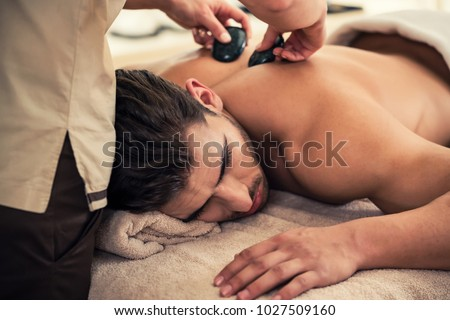 Handsome young man relaxing under the stimulating effect of a traditional hot stone massage at luxury spa and wellness center #1027509160