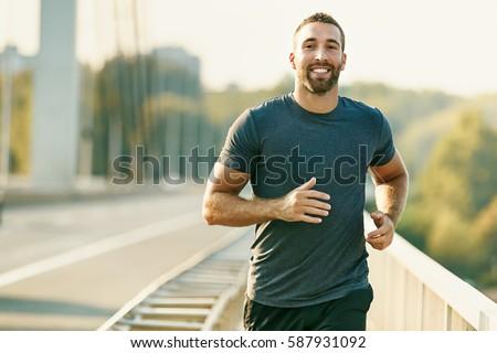 Handsome young man running across the bridge.