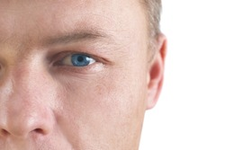 Handsome young man's face with blue eyes. Close up portrait on white background