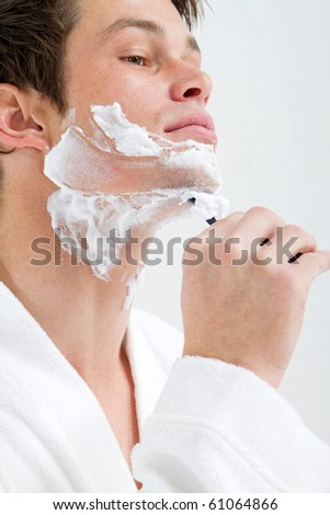 handsome young man shaving in morning