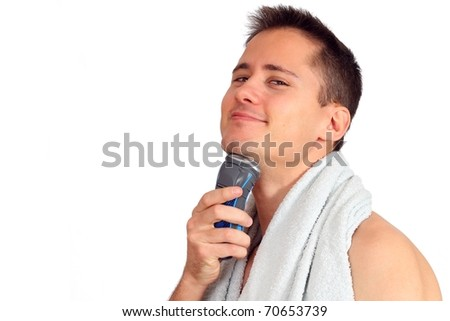 Handsome young man shaving with electric shaver