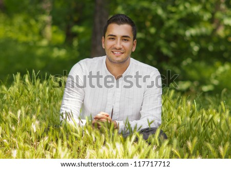 Handsome young man siting on meadow, outdoor shot
