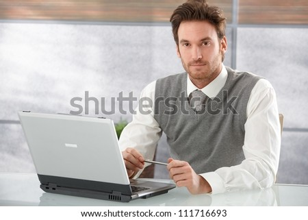 Handsome young man sitting at desk in modern office, working on laptop.