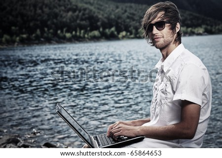 Handsome young man sitting near the sea with a laptop. - stock photo