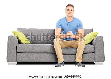 Handsome young man sitting on a modern sofa isolated on white background #259449992