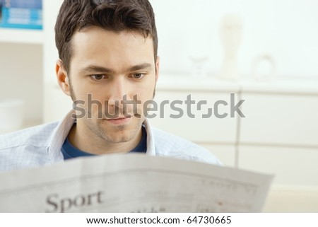 Handsome young man sitting on couch at home reading sport news in newspaper.?