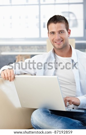 Handsome young man sitting on sofa at home, using laptop.?