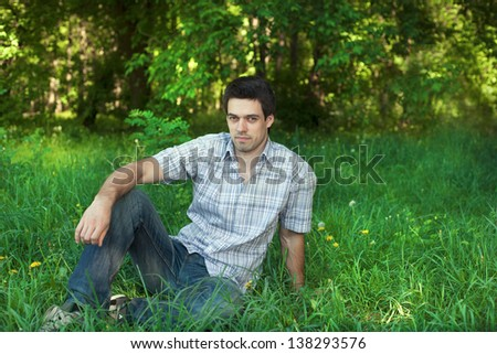 Handsome young man sitting on the grass at the park #138293576
