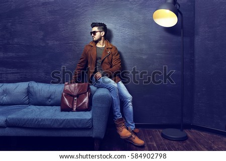 Handsome young man sitting on the sofa. Jacket, boots, jeans, sunglasses.