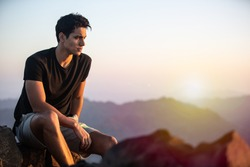 Handsome young man sitting on top of a mountain at beautiful sunset.