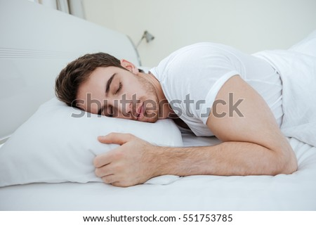 Handsome young man sleeping on pillow in bed