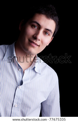 Handsome young man smiling. Isolated on black background. - stock photo