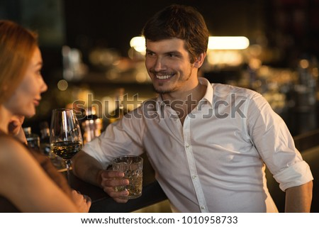 Handsome young man smiling seductively at the beautiful woman at the bar flirtatious flirting sexuality seductive sensuality affection lifestyle party drinking restaurant communication couples