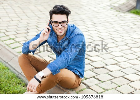 handsome young man smiling while talking on a smart-phone outdoors