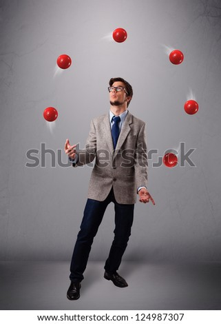 handsome young man standing and juggling with red balls