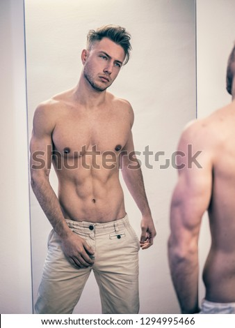 Handsome young man standing in his bedroom, dressing, while looking at himself shirtless in the mirror