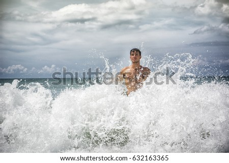 Handsome young man standing on a beach in Phuket Island, Thailand, getting hit by big wave's splash #632163365