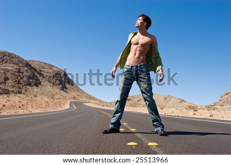 Handsome young man standing on road