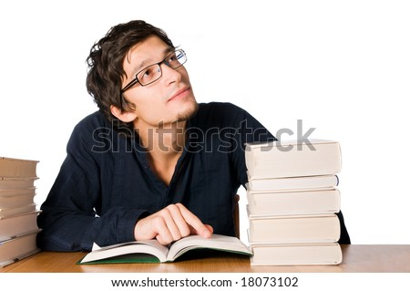Handsome young man studying and dreaming between stacks of books on table.