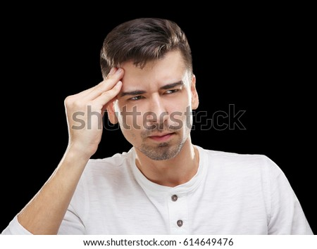 Handsome young man suffering from headache on black background #614649476
