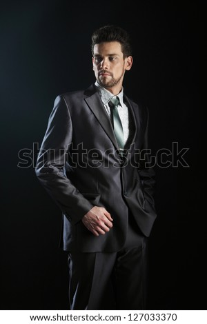 Handsome young man suit casual necklace suit isolated on black