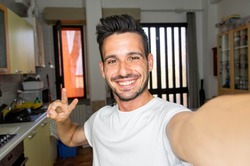 Handsome young man taking a selfie at home using smart phone device - Happy guy smiling in the camera indoor
