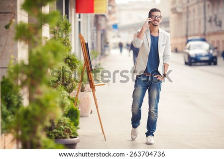 Shutterstock Handsome young man talking on the phone while walking on the street
