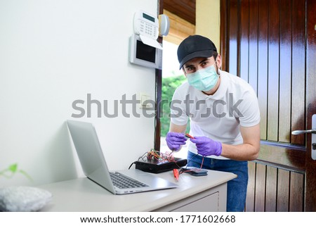 handsome young man telephone operator worker fixing internet issue connexion at client house with surgical mask and gloves during pandemic period Photo stock ©