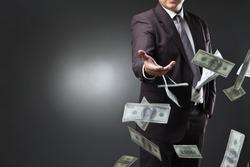 Handsome young man throwing money over dark background