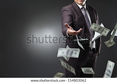 Handsome young man throwing money over dark background #154803062