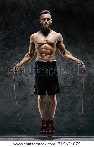 Handsome young man training with his skipping rope. Photo of sporty muscular man with perfect body on dark background. Best cardio workout