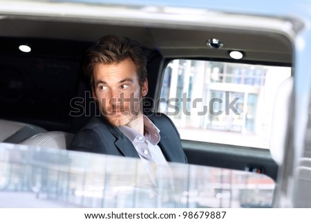 Handsome young man traveling in limousine, looking out of window. - stock photo