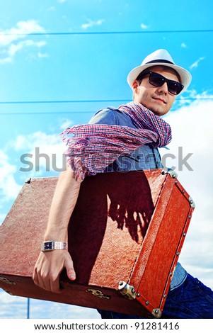 Handsome young man walking along railroad. - stock photo