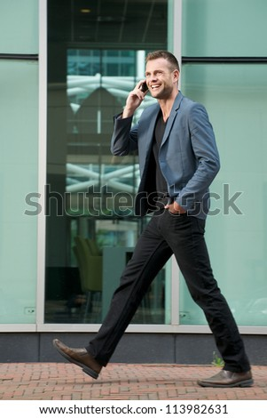 Handsome young man walking and talking on the phone