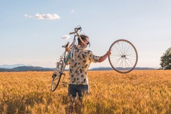 Handsome young man walks in the middle of a harvest field. He's carrying a bike without a wheel. He's wearing a trendy shirt. He's pointing to the side.