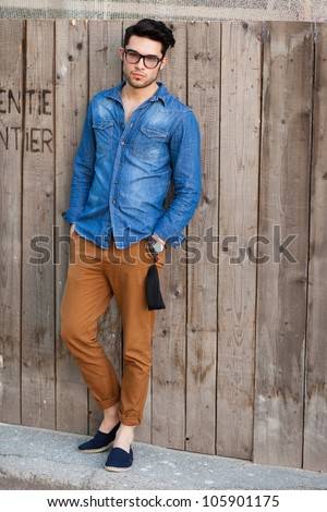 handsome young man wearing glasses posing outdoors