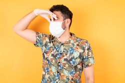 Handsome young man wearing hawaiian shirt standing over yellow isolated background smelling something stinky and disgusting, intolerable smell, holding breath with fingers on nose. Bad smell