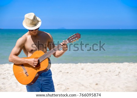 Handsome young man wearing sunglasses and playing guitar on summer vacation playing guitar near the beach beautiful. Smiling playing acoustic guitar at bright sky #766095874