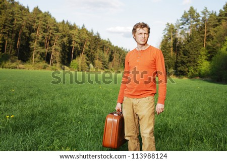 Handsome young man with a suitcase standing in the sunshine in a green grassy field with pine trees in the distance