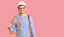 Handsome young man with bear wearing architect hardhat holding build project looking positive and happy standing and smiling with a confident smile showing teeth