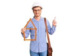 Handsome young man with bear wearing architect hardhat holding build project surprised with an idea or question pointing finger with happy face, number one